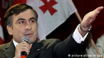 Saakashvili pointing to the right with a Georgian flag in the background