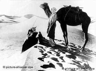 A black-and-white picture of a man in a turban and a camel in the desert