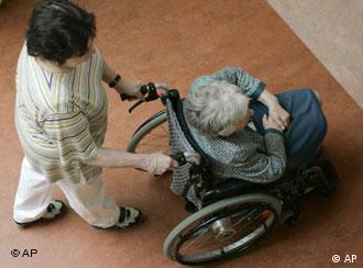 A carer pushes an elderly woman in a wheelchair
