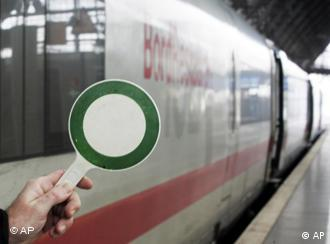 A conductor gives a green flag to a DB train
