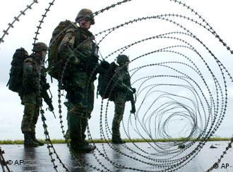 German soldiers stand behind barbed wire at an army base in Wilhelmshaven in Germany