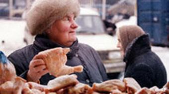 Woman examines chicken at a market