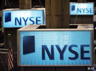 Lighted NYSE signs sit atop trading post on the floor of the New York Stock Exchange