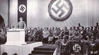 Hitler, surrounded by swastikas, making a speech