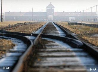 Two people walk behind barbed wire at the Auschwitz concentration camp