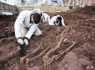 Forensic experts work around skeletons on the constructuion site
