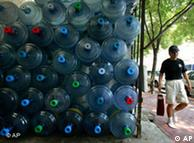 Ein Mann läuft an aufeinander gestapelten Flaschen mit Trinkwasser vorbei (Archiv, Quelle: AP)