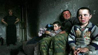 Chechen father Alkhazur Ibragimov, second right, sits with his sons Salman, left, and Imran, right, as his wife Zarema, far left, looks on in their home in the Chechen capital Grozny, Tuesday, April 10, 2007. Ramzan Kadyrov, who was sworn in as Chechnya's new president earlier this month, vowed to bring prosperity to the region wracked by two wars, growing Islamic extremism and grinding poverty since the Soviet collapse. (AP Photo/Musa Sadulayev)