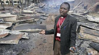 Bishop Sospeter Njenga surveys a row of houses belonging to Kikuyus, which were burned to the ground