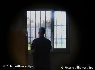 a man looking out a prison window