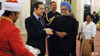 Sarkozy and Singh stand in a room surrounded by other people