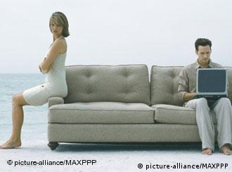 A couple sitting apart on a sofa