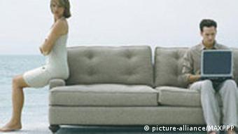 Ein Mann sitzt mit einem Laptop auf dem Sofa, eine Frau sitzt abgewandt auf der Kante des Sofas