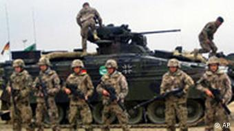NATo troops stand in front of a tank