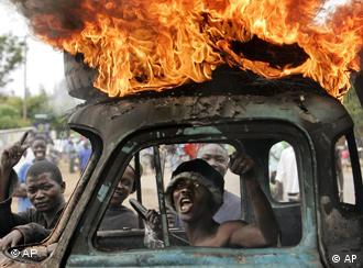 A man sits in the cab of a destroyed truck in kenya in riots