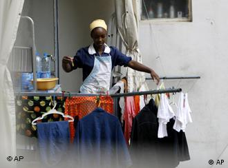 A maid hangs clothes on a balcony in Beirut, Lebanon