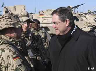 Germany's Defense Minister Franz-Josef Jung left talks to German ISAF soldiers during his visit to Camp
