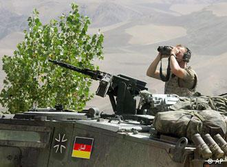 A German soldier looking through binoculars from a miliatary tank in Afghanistan