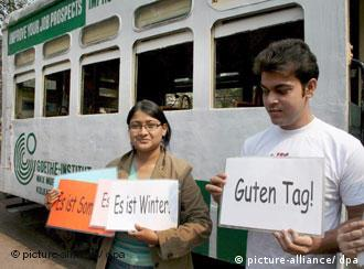 Two Indians holding signs saying Good day in German outside a Goethe Institute bus