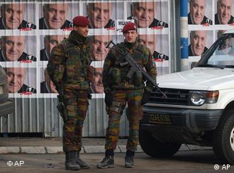 Belgian soldiers serving in KFOR walk past election posters