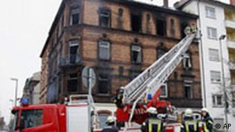 Firefighters inspected the burnt out house in Ludwigshafen on Monday, Feb. 4, 2008. At least nine people, including five children, died in a fire at a four-story apartment building in southwest Germany, police said Monday.