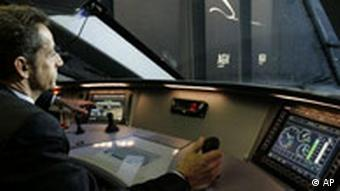France's President Nicolas Sarkozy sits at the wheel of a high-speed train