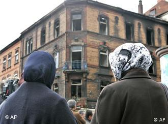 Two Turkish women in headscarves observe the site of the fire