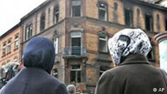 Two women with headscarves gaze at the building where the fire broke out in Ludwigshafen