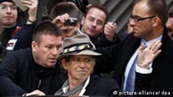 Der Rolling Stone-Gitarrist Keith Richards wird von Security-Personal abgeschirmt und winkt seinen Fans