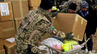 A German soldier with the International Security Assistance Force (ISAF) places a package of relief goods on a wheel barrel