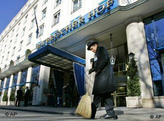 A hotel employee sweeps the street prior to the conference