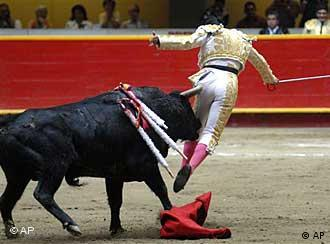 A bullfighter getting gored in the behind by a bull