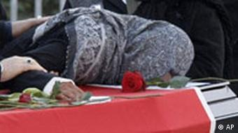 A woman mourns at the coffin with the remains of a victim killed by a fire in front of the burnt house in Ludwigshafen, Germany, Sunday, Feb. 10, 2008.
