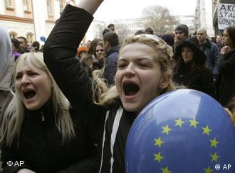A girl carrying an EU baloon shouts slogans during a protest rally in Belgrade