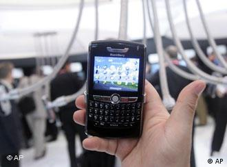 A BlackBerry cell phone in a person's hand