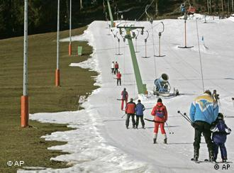A ski lift with people while the snow on the ground to the left has already melted