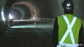 A construction worker walking down a tunnel