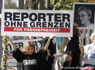 Menschenrechtsaktivisten bei einer Gedenkveranstaltung für Anna Politkowskaja in Berlin halten ein Plakat von den Reportern ohne Grenzen hoch (Foto: dpa)