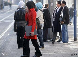 Women in headscarves wait at a bus stop