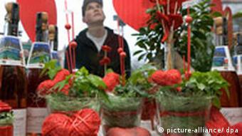 A passerby looking at a flower-shop displays for Valentine's Day, decorated with red hearts