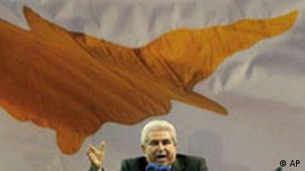 President Dimetris Christofias of Cyprus stands at a podium in front of a large Cypriot flag.