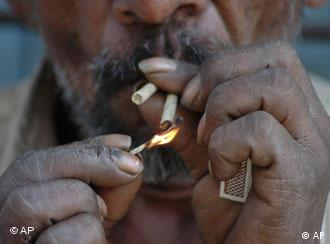 An Indian worker lighting a bidi -- a pleasure that is now banned in public
