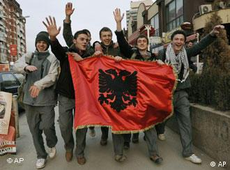 Kosovo Albanians walk with an Albanian flag as they celebrate Kosovo's expected declaration of independence in downtown Pristina, Kosovo, Friday, Feb. 15, 2008