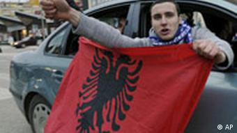 Kosovo Albanians display an Albanian flag while driving their car celebrating the upcoming independence of Kosovo in downtown Prishtina
