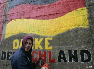 Man unrolls Kosovan flag in front of his shop