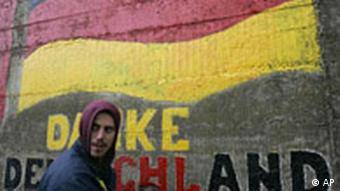 A man paints a slogan reading 'Thank You Germany' below an image of the German flag, on a wall in Gnjilane, Kosovo