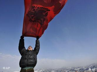 A Kosovar Albanian man holds an Albanian flag on his roof-top over the ethnically divided town of Kosovska Mitrovica, Kosovo as he celebrates