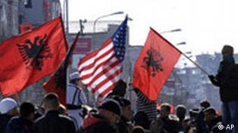 Kosovar Albanians wave U.S. and Albanian flags on the Albanian side of the ethnically divided town of Kosovska Mitrovica to celebrate the independence of Kosovo