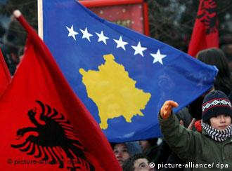 People dance with the Albanian and Kosovo flag while celebrating