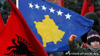 Kosovo Albanians celebrate independence,waving Albanian natioanl flag (L) and new Kosovo's flag